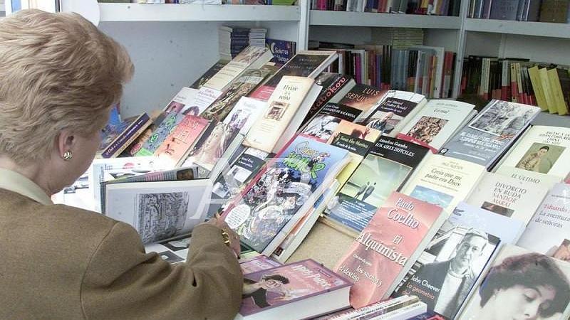 Madrid. 07/06/2002. Una mujer hojea los libros en una de las casetas de la Feria