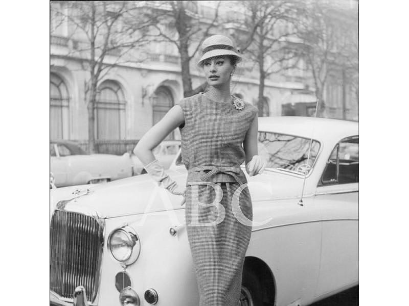 París (Francia), 1959. Modelo de la temporada primavera verano: falda y blusa de pata de gallo de Rodier. El resto de los accesorios y complementos son de Christian Dior