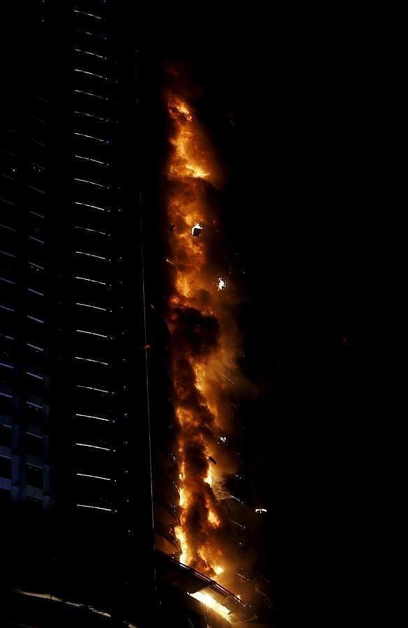 Los cascotes caen durante el incendio en el rascacielos de Dubai