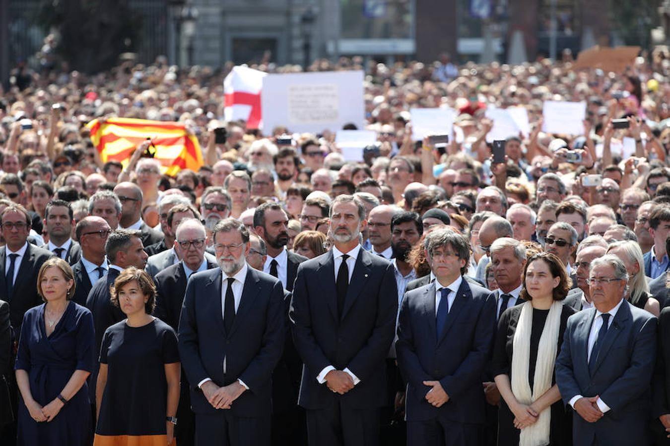 El rey Felipe VI, acompañado de la vicepresidenta del Gobierno, Soraya Sáenz de Santamaría, el presidente del Ejecutivo, Mariano Rajoy, el presidente de la Generalitat, Carles Puigdemont, la alcaldesa de la ciudad, Ada Colau y el ministro de Interior, Juan Ignacio Zoido, guardan un minuto de silencio en la Plaza de Cataluña