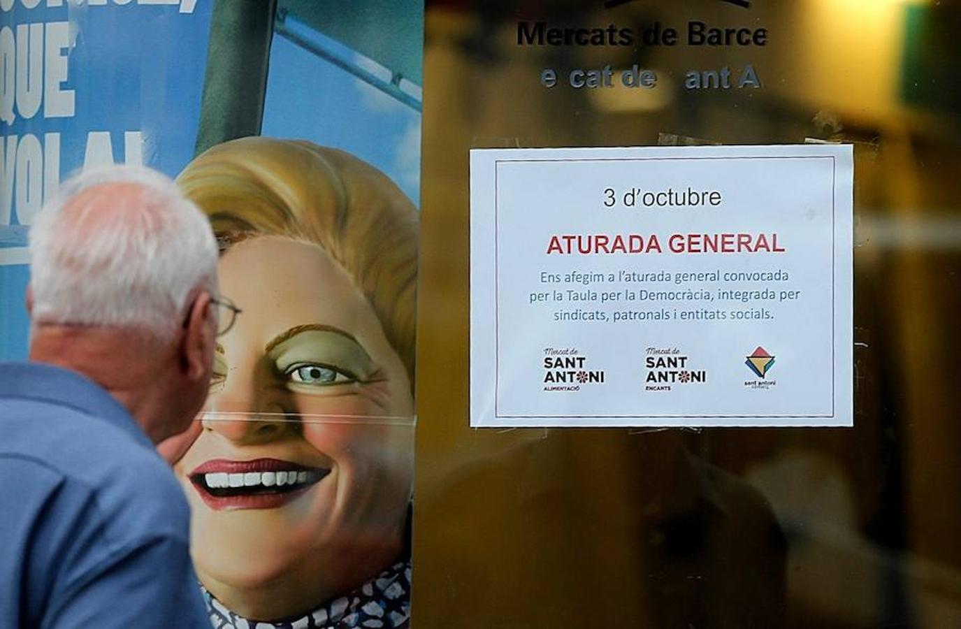 Un hombre ante las puertas del Mercado de Sant Antoni que permanece cerrado por la huelga general convocada para hoy en Cataluña