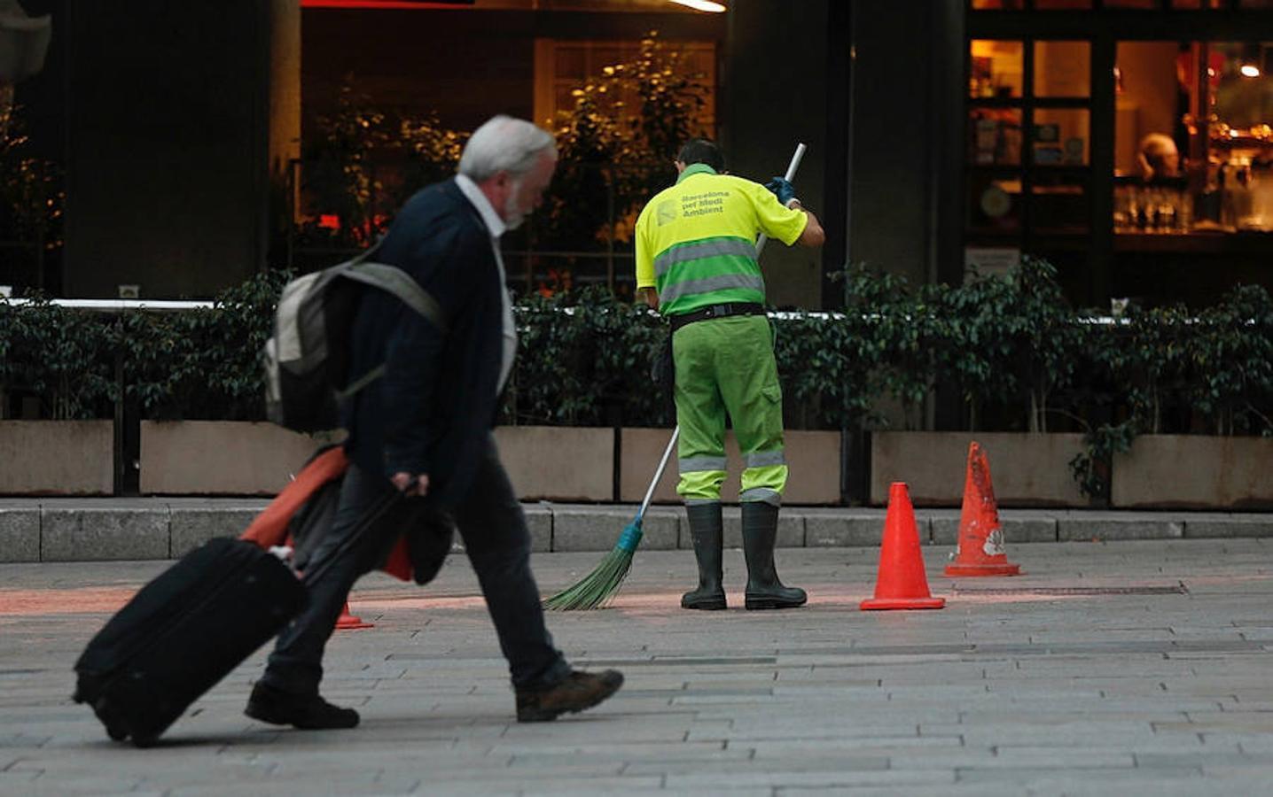 Un trabajador del Servicio de Limpieza realiza su tarea en las inmediaciones del Mercado de Sant Antoni, que permanece cerrado por la huelga general convocada para hoy en Cataluña