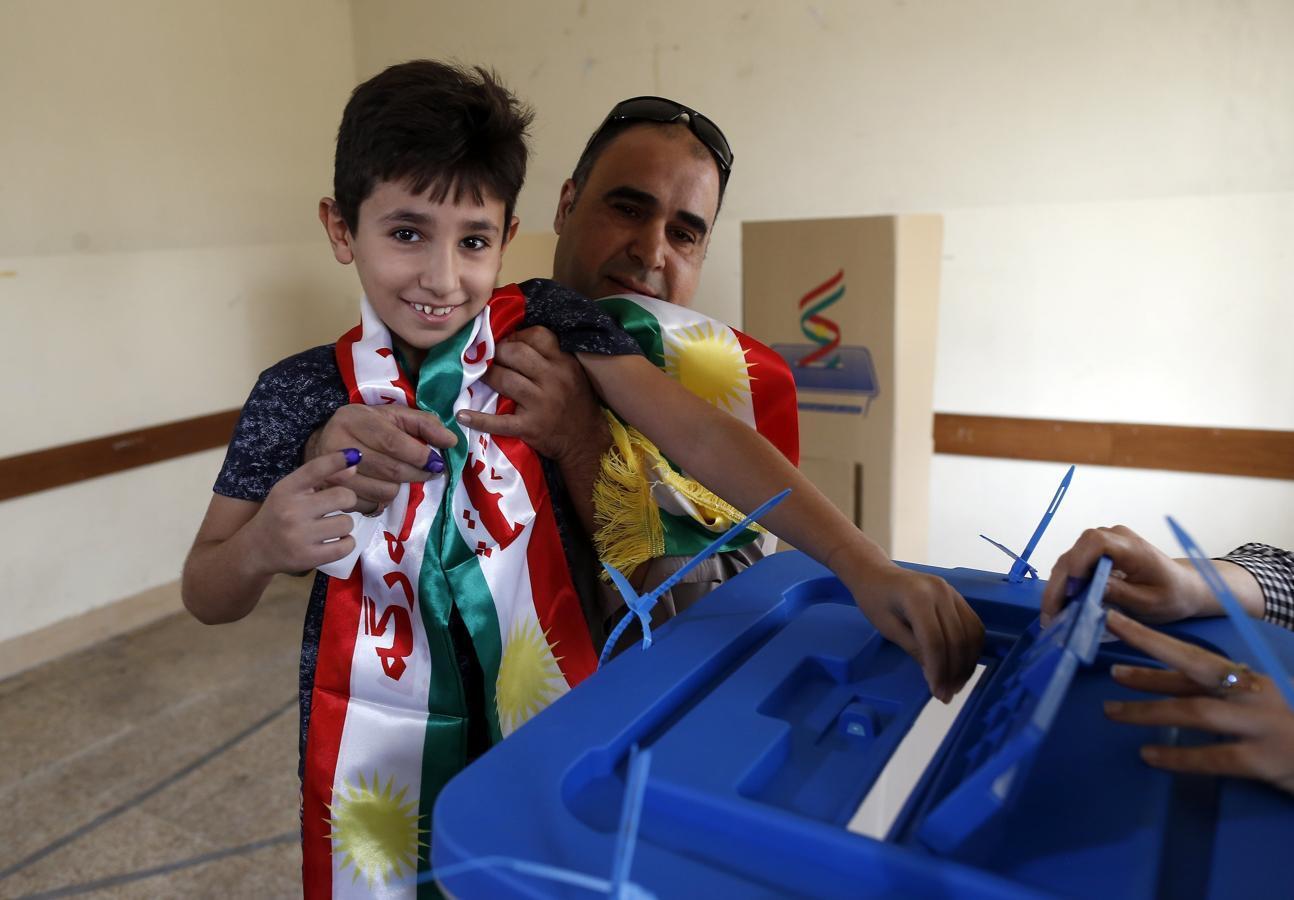 Un niño iraquí coge una papeleta para su padre antes de votar en el referéndum de independencia en un centro electora