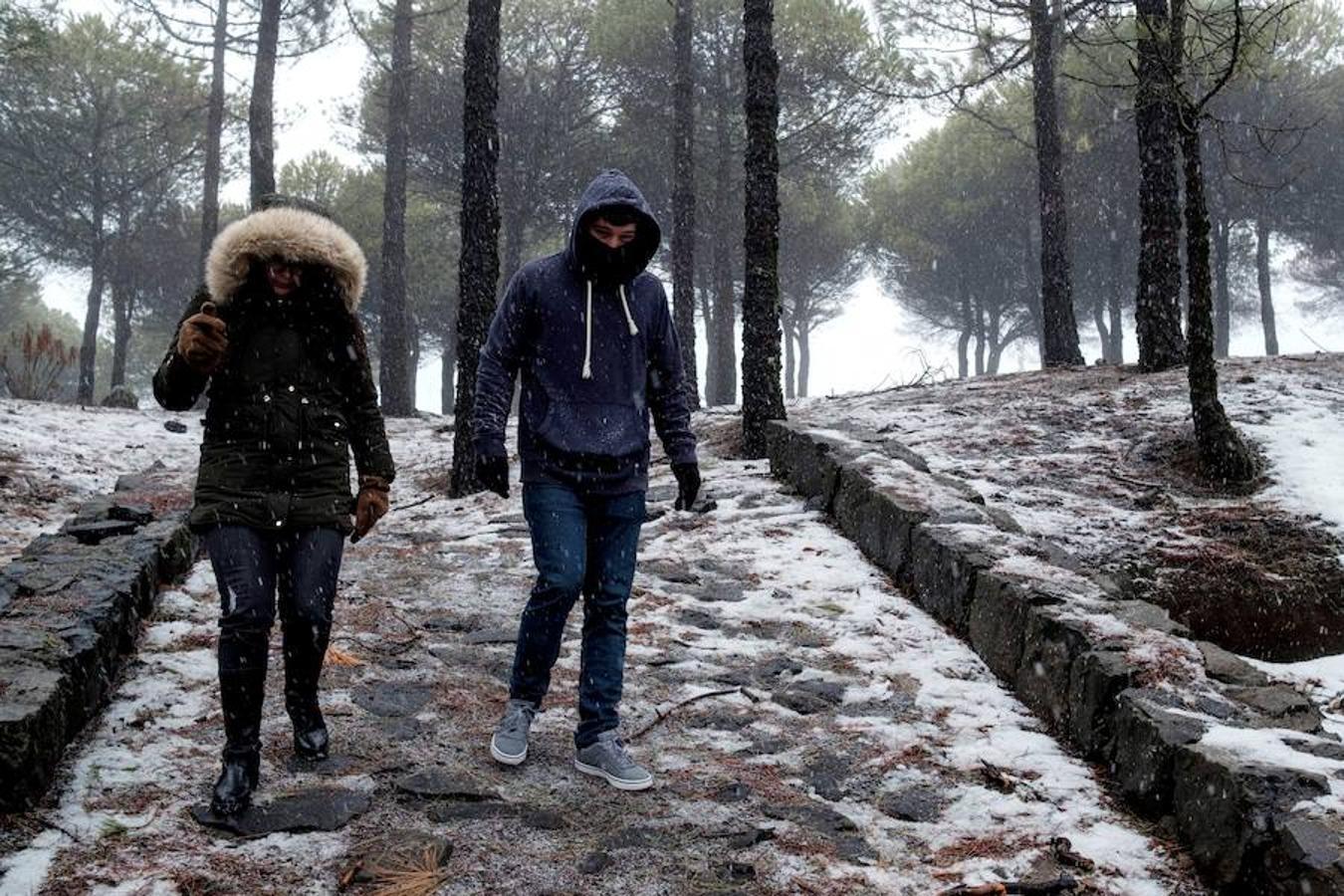 Dos personas caminan bajo precipitaciones en forma de nieve en Tejeda, en la provincia de Las Palmas de Gran Canaria.