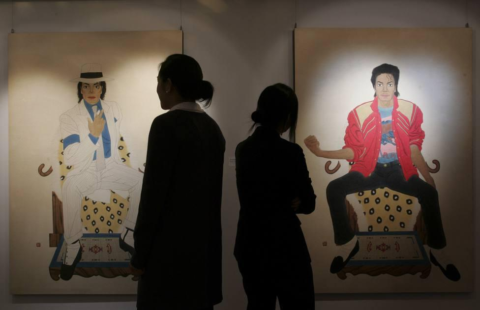 "Staff members of Seoul Auction poses in front of ""Portrait of the King"" depicting the late pop star Michael Jackson during a private sales exhibition in Hong Kong -0051POH5.JPG-"
