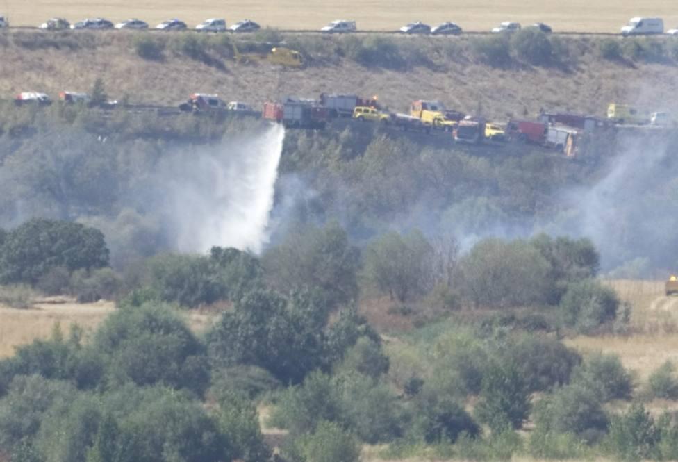 Los bomberos intentan extinguir el fuego causado por el accidente